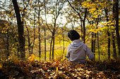 A lonely boy sitting among the leaves in the autumn forest. Picture taken from behind.