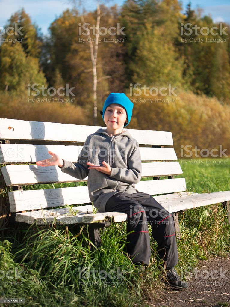 Lonely boy sitting on a bench in a cap stock photo