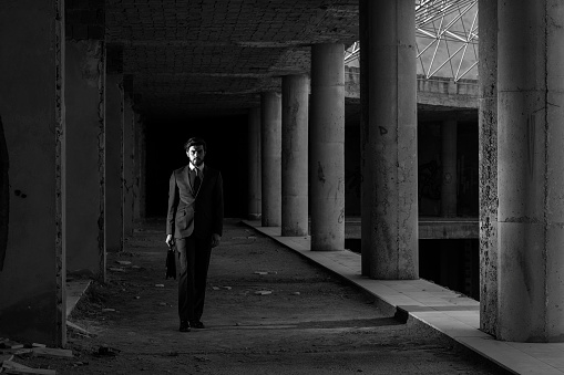 Full length black and white portrait of lonely businessman wearing suit in abandoned modern building.Group of columns are seen in diminishing perspective.Model is standing on the left side of horizontal frame.Main light is positioned on the left side of model.Shot with a full frame DSLR camera.