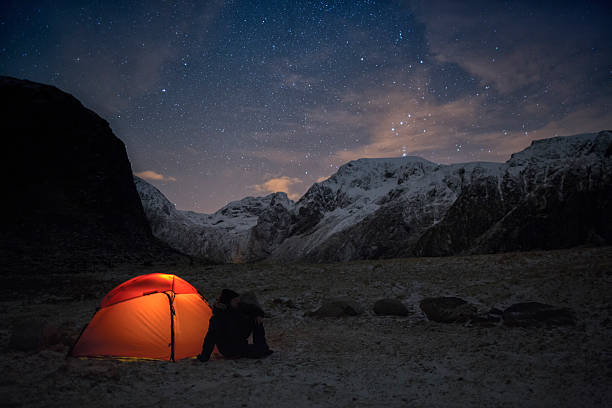Lonely camper looking at the starry sky in wintertime stock photo