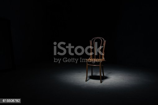 Lonely chair in the spot of light on black background at empty roomLonely chair in the spot of light on black background at empty room