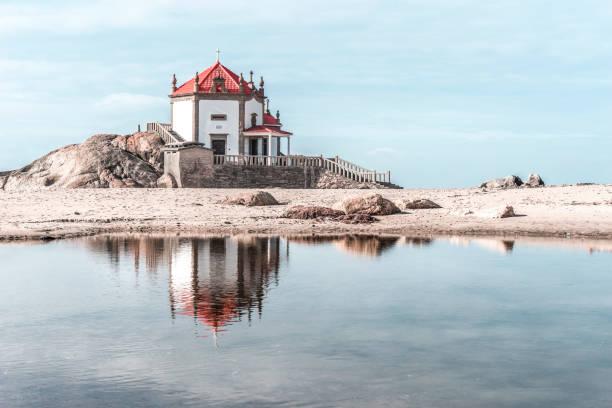 lonely chapel on the beach reflected in the water, aveiro - aveiro imagens e fotografias de stock