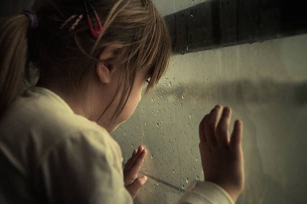 lonely child looking through window - low contrast stock pictures, royalty-free photos & images