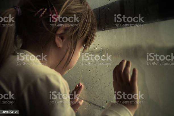 Photo of Lonely child looking through window