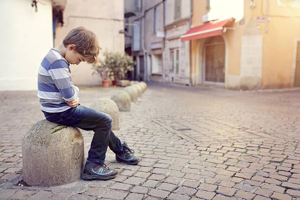 lonely child sitting on a street corner - criança perdida imagens e fotografias de stock
