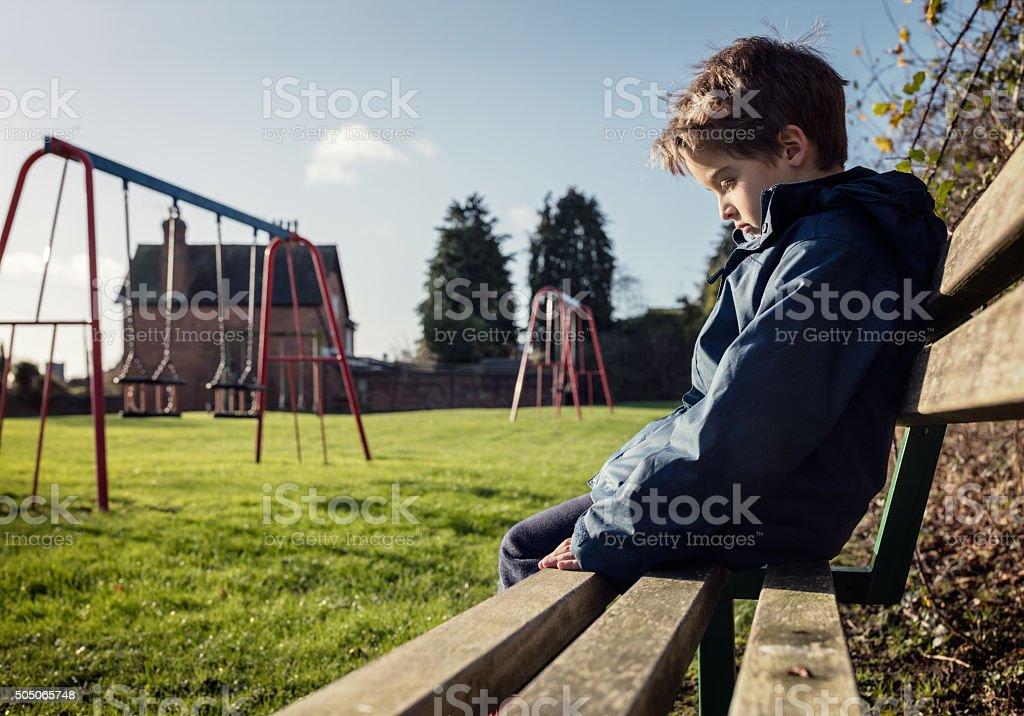 Lonely niño sentado en el banco en el parque de juegos jugar - foto de stock