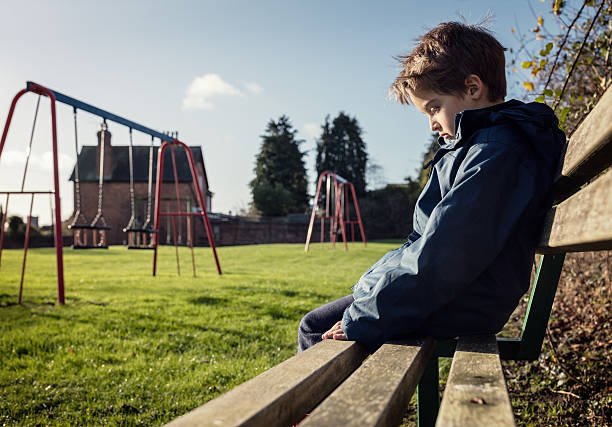 lonely child sitting on play park playground bench - boys stock photos and pictures