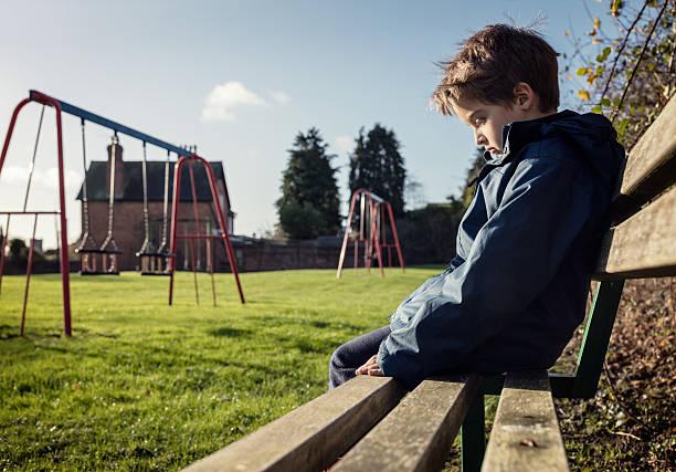 enfant solitaire assis sur parc de banc aire de jeu - petits garçons photos et images de collection