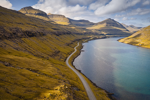 Lonely empty country road along Funningsfjordur Fjord in late summer, Aerial Drone Point of view along the rural national road on Funningsfjørður on Eysturoy Island in between green hills and North Atlantic Ocean Fjord Inlet. Funningsfjørður Fjord, Eysturoy Island, Faroe Islands, Kingdom of Denmark, Nordic Countries, Scandinavia, Europe.