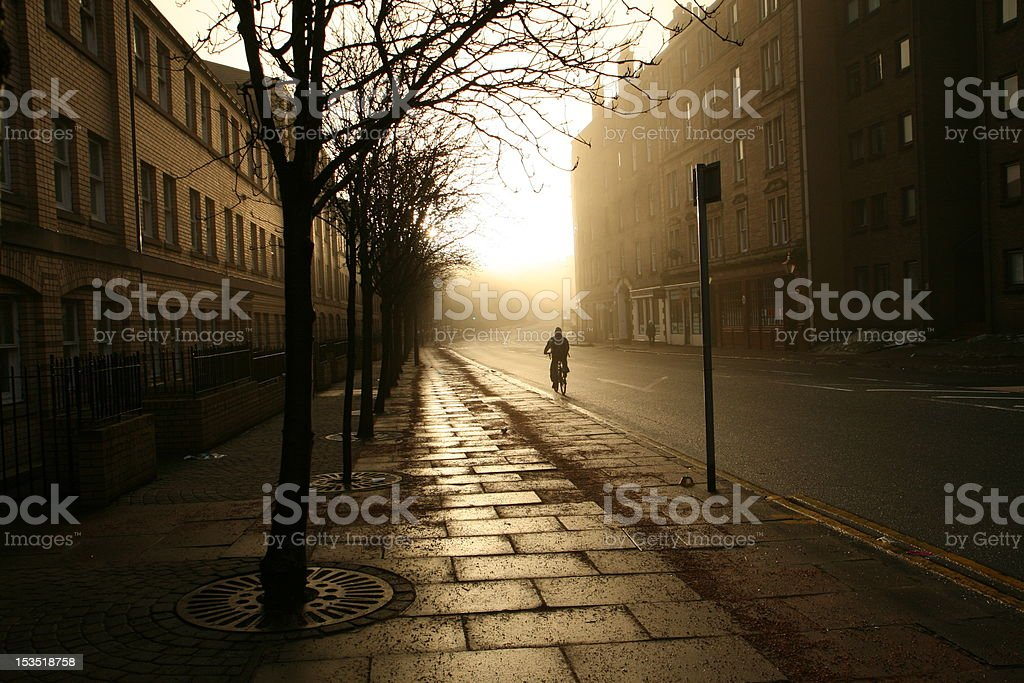 Lonely cyclist sunlit in empty streets of Edinburgh at dawn royalty-free stock photo