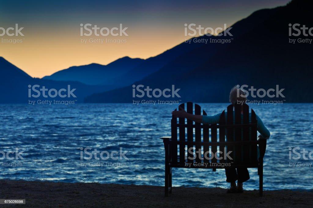 Silhueta de mulher viúva divorciada solitária deprimido ao pôr do sol - foto de acervo