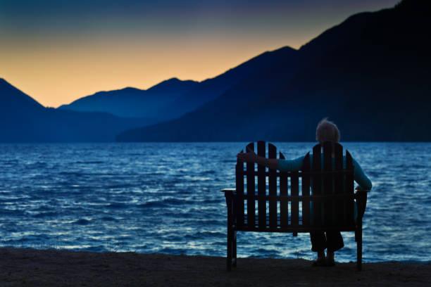 silhouette femme veuf divorcé déprimé solitaire au coucher du soleil - veuve photos et images de collection