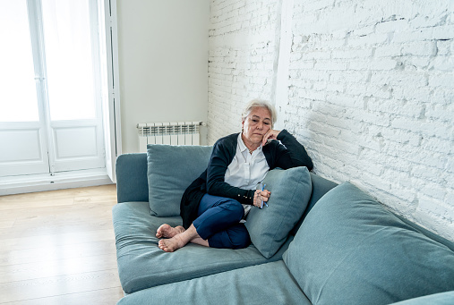 874789168 istock photo Lonely depressed senior old widow woman crying on couch in isolation at home, feeling sad and worried missing husband and family in COVID-19 Outbreak, lockdown, social distancing and Mental health. 1251789901