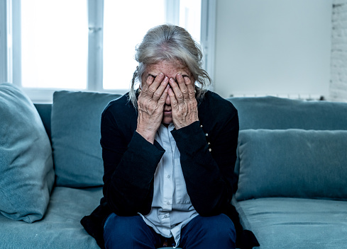 874789168 istock photo Lonely depressed senior old widow woman crying on couch in isolation at home, feeling sad and worried missing husband and family in COVID-19 Outbreak, lockdown, social distancing and Mental health. 1251789902