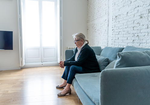 874789168 istock photo Lonely depressed senior old widow woman crying on couch in isolation at home, feeling sad and worried missing husband and family in COVID-19 Outbreak, lockdown, social distancing and Mental health. 1251790424