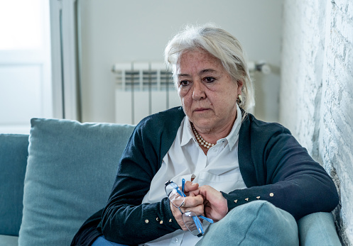 874789168 istock photo Lonely depressed senior old widow woman crying on couch in isolation at home, feeling sad and worried missing husband and family in COVID-19 Outbreak, lockdown, social distancing and Mental health. 1251790502