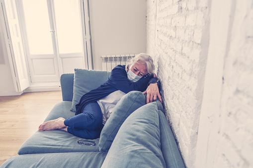 874789168 istock photo Lonely depressed senior widow woman with protective mask crying on couch isolated at home, sad and worried missing husband and family in COVID-19 death, lockdown, social distancing and Mental health. 1251790423
