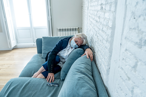 874789168 istock photo Lonely depressed senior widow woman with protective mask crying on couch isolated at home, sad and worried missing husband and family in COVID-19 death, lockdown, social distancing and Mental health. 1251790499