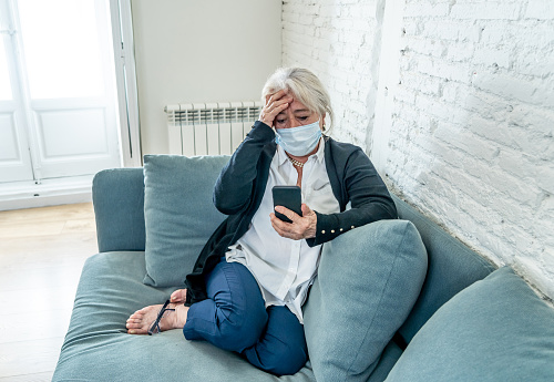 874789168 istock photo Lonely depressed senior widow woman with protective mask crying on couch isolated at home, sad and worried missing husband and family in COVID-19 death, lockdown, social distancing and Mental health. 1251791592