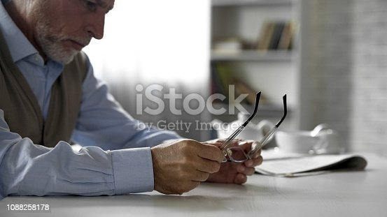 istock Lonely elderly man sitting at table taken off his glasses, eyesight problems 1088258178