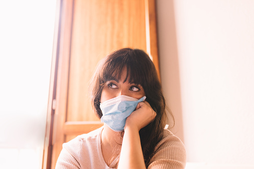 Lonely female at home in protective sterile medical mask on her face looking at window, bored woman. Chinese pandemic coronavirus, virus covid-19. Quarantine, prevent infection concept.