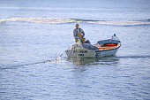 19th October, 2018 - Self employed fisherman gathering nets into his small boat just off Brownsea Island, Poole in Southern England
