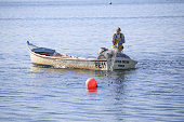 19th October, 2018 - Lonely fisherman gathering nets into his small boat just off Brownsea Island, Poole in Southern England