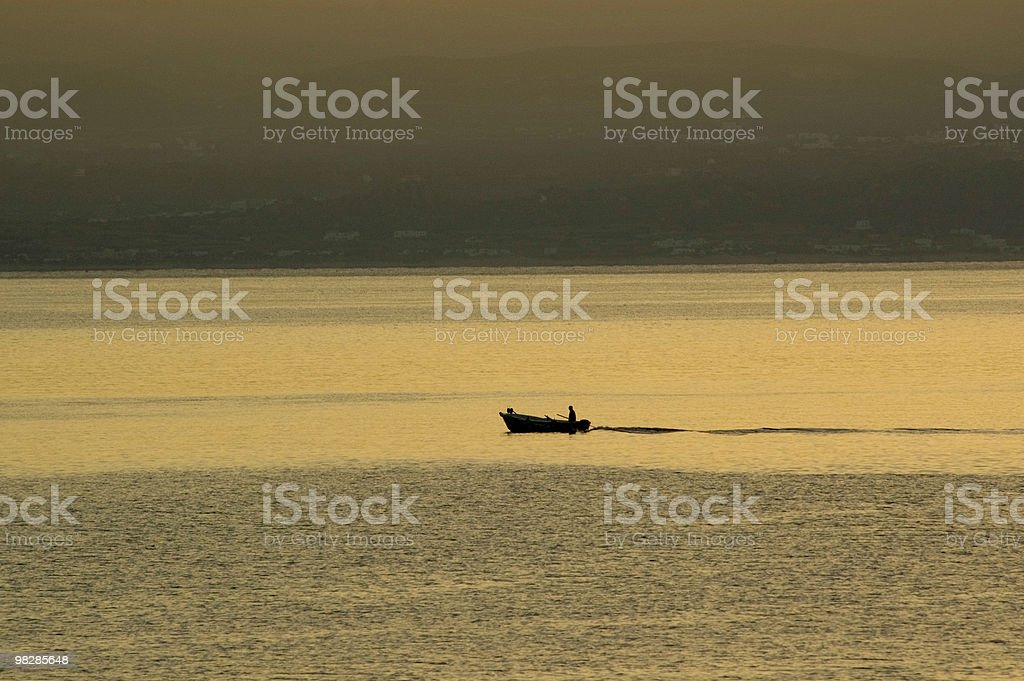 Lonely fisherman on his boat fishing in a summer morning royalty-free stock photo