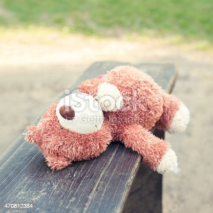 istock Lonely forgotten teddy bear toy lying on the bench. 470812384