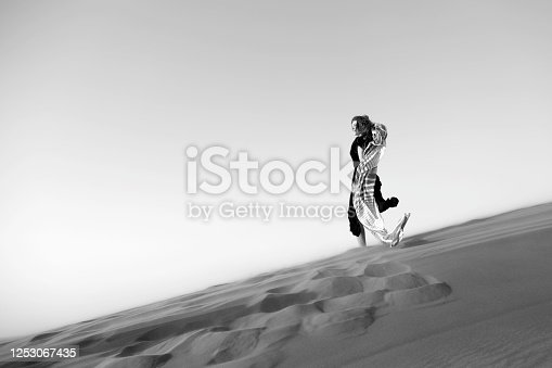 Caucasian woman in a black dress descends from a mountain in the desert. Black and white shot