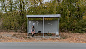 A lonely girl in a dress and boots sits at a bus stop.