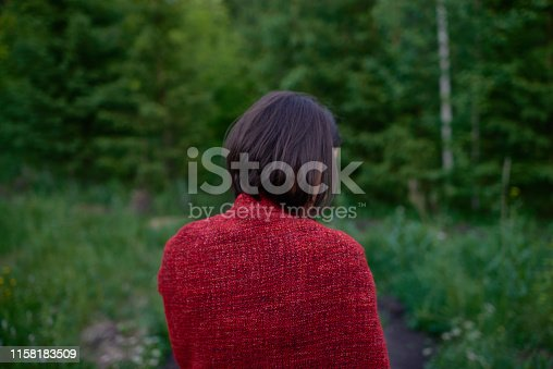 Back view of brunette in red plaid standing alone on blurred background of green woods