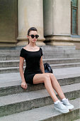 Sensual girl, like a doll, sits on the stairs in the city, in a black dress with sunglasses. Full length portrait.