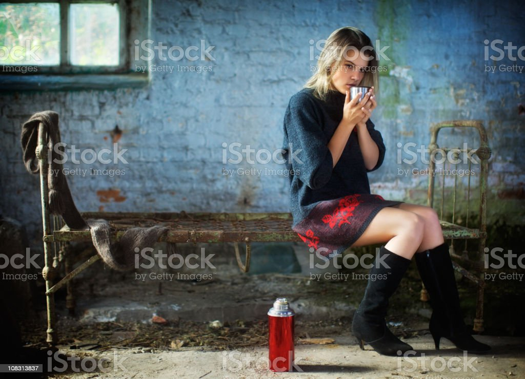 Lonely girl sits in an old house and drink tea. royalty-free stock photo