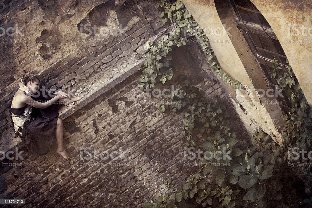 Lonely girl sitting on the wall stock photo