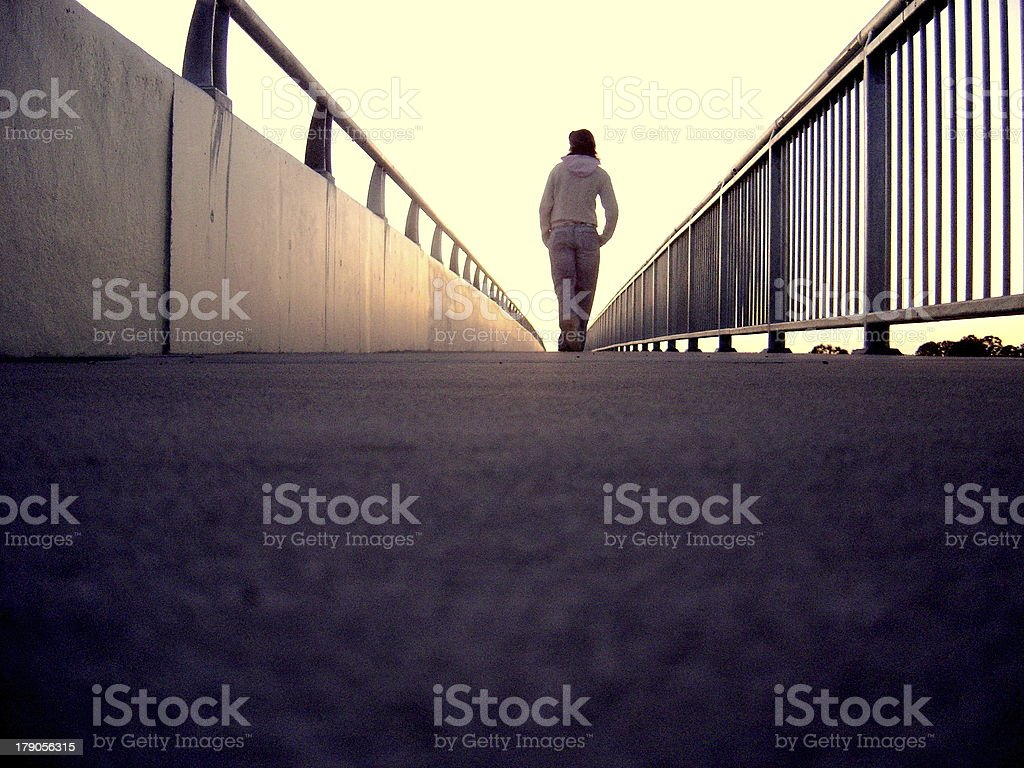 Lonely Girl walking along Bridge royalty-free stock photo