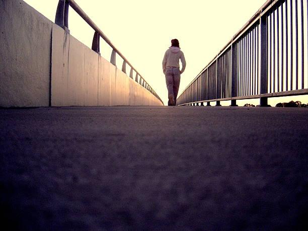 Lonely Girl walking along Bridge stock photo