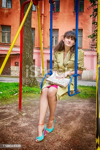 Lonely girl with a book sitting on a swing in an old courtyard. Bright toned image