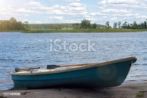 Green empty rowing boat on the river shore country side overcast background. Wild life concept