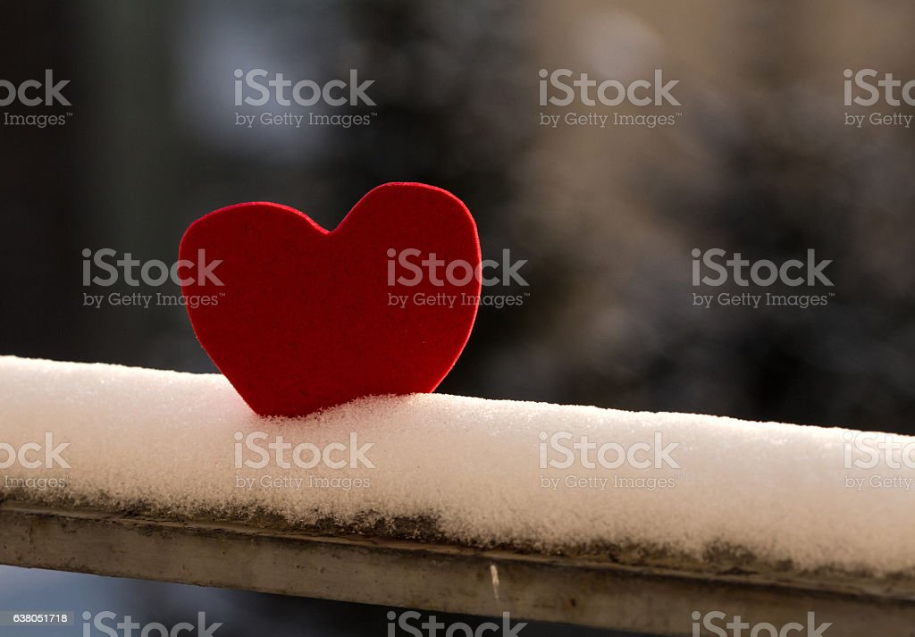 Lonely heart on snowy railing stock photo