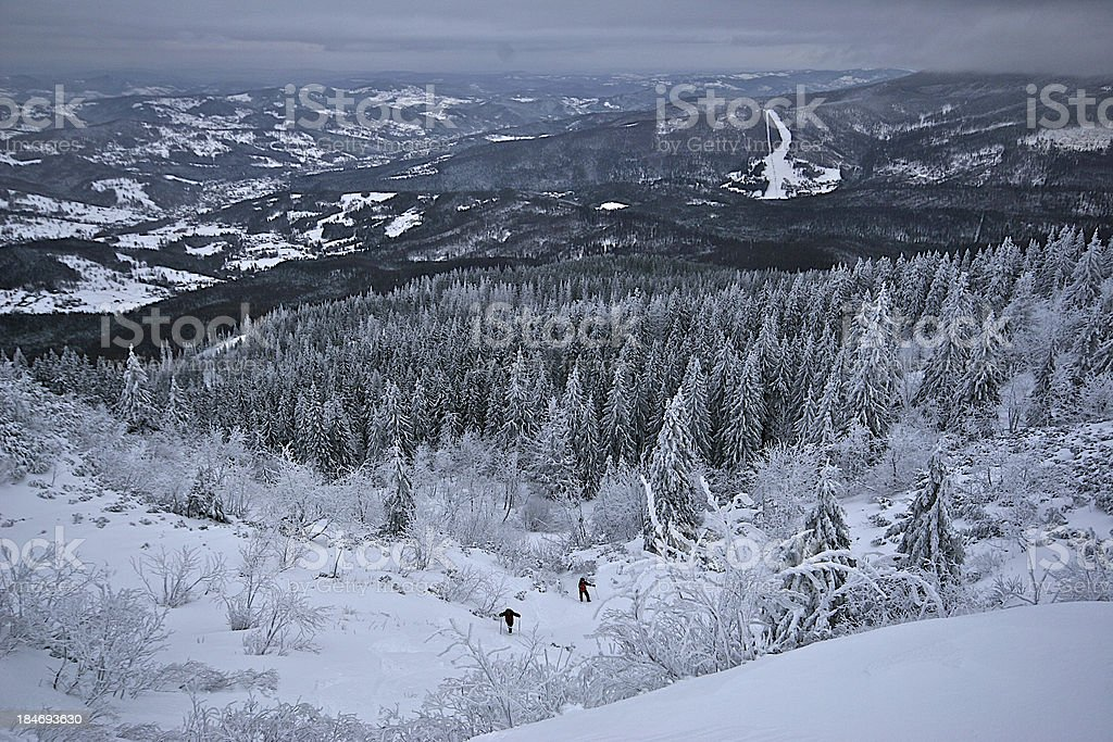 Lonely hikers wade through deep snow in mountain royalty-free stock photo
