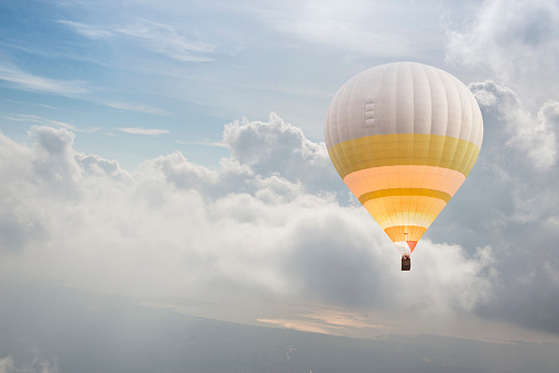 Lonely hot air balloon flying above the clouds