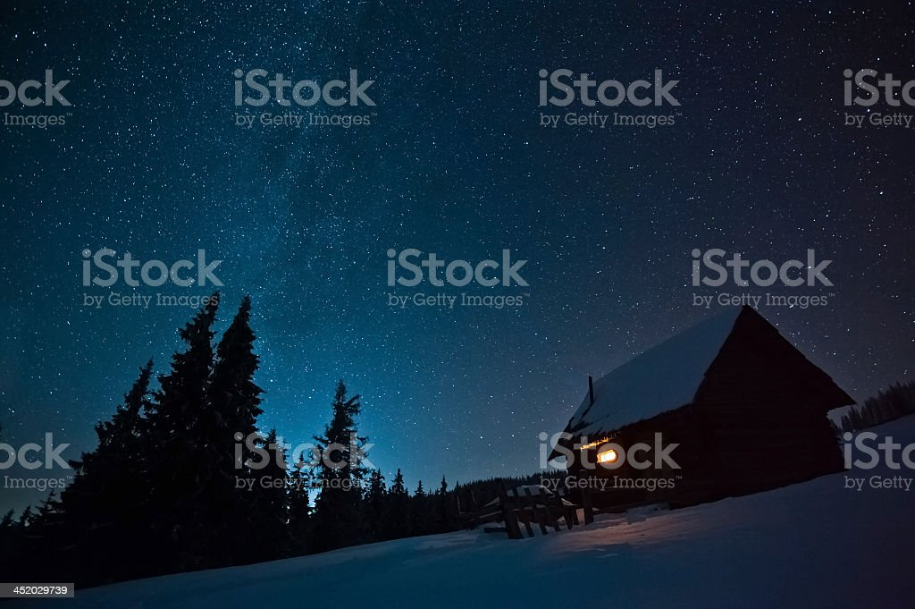 Lonely house covered in snow among forest at night stock photo