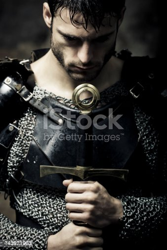 Mystical portrait of meditative Knight with sword,selective focus, very creative color retouching and hard lighting to underline the ancient medieval time,vignetting and possible noise,low key