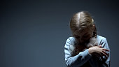 Lonely little child hugging teddy bear, bullying concept, dark background