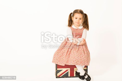 926982852 istock photo Lonely little girl with old suitcas 528485216