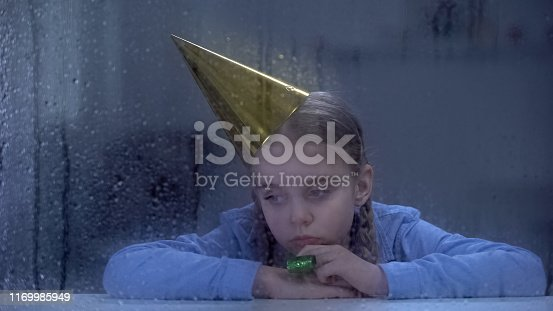 Lonely little orphan in birthday hat with party blower behind rainy window