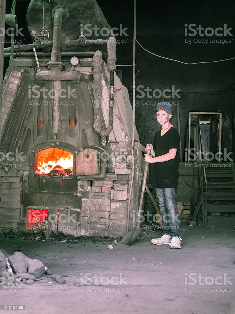lonely little poor boy which holding a shovel stock photo