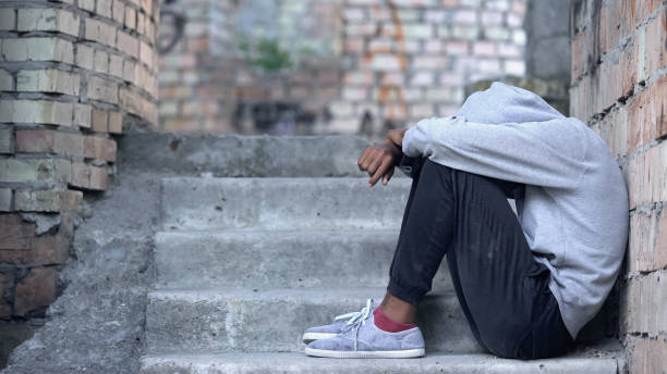 Lonely male teen sitting building stairs, misunderstanding depression, problem Lonely male teen sitting building stairs, misunderstanding depression, problem homelessness stock pictures, royalty-free photos & images