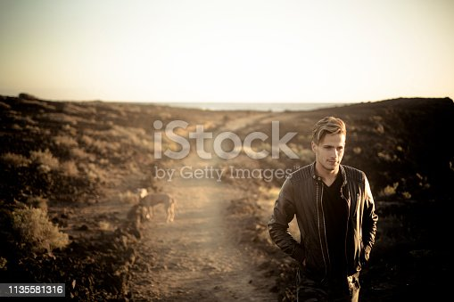Lonely man and best friend dog walking together on a path in outdoor desert leisure activity with ocean in background at the end - friendship and travel concept for people with animals